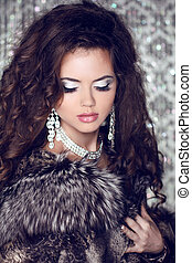 Beautiful woman with long brown hair in luxury fur coat. Closeup portrait of a fashion model posing at studio.