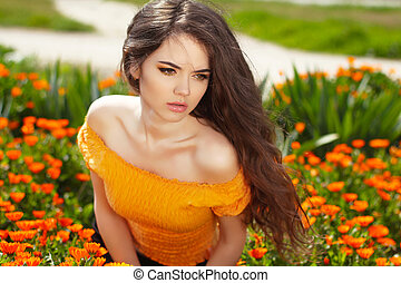 Beautiful woman with long brown hair over flowers field. Closeup outdoors portrait.