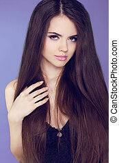 Beautiful woman with long brown hair. Closeup portrait of fashion