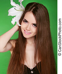 Beautiful woman with long brown hairstyle and flower in hair. Attractive smiling girl isolated on green