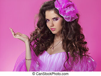 Beautiful woman with long curly hair style over pink