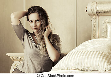 Beautiful woman with long curly hairs in a bedroom