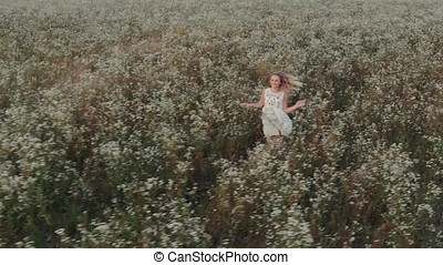 Beautiful woman with long hair in a white dress running in a field
