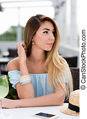 Beautiful woman with long hair in blue gentle dress. Sits cafe table. Emotions of tenderness lightness of spring and summer. Tanned skin casual makeup. Waiting for lunch dinner order in a restaurant.
