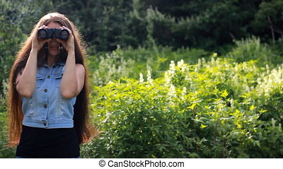Beautiful woman with long hair looking through binoculars