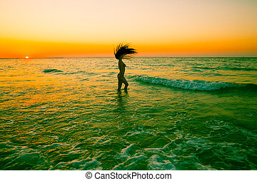 Beautiful woman with long hair on sunset on beach. Persian Gulf ,Dubai.Tanning girl near ocean, tropical resort, summer holiday