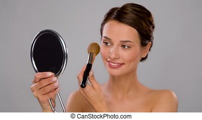 beautiful woman with mirror and makeup brush - beauty and ...