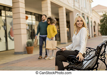 Beautiful woman with mobile phone sitting on the bench