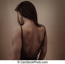 Beautiful woman with naked back in dress posing on dark...