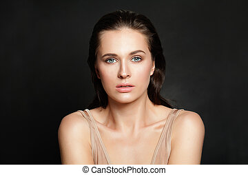 Beautiful woman with natural clear skin on black background
