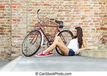 Beautiful woman with old bike in front of a brick wall