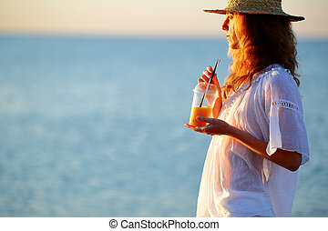 Beautiful woman with orange juice in disposable cup against the sea
