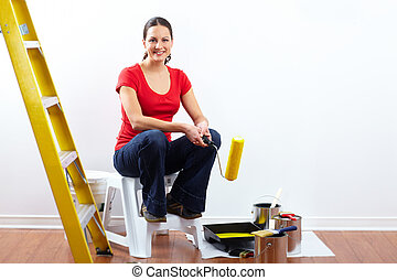Beautiful woman with painting roller.