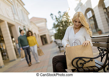 Beautiful woman with paper shopping bag sitting on the bench