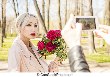 Beautiful woman with peony flowers, outdoors portrait