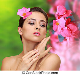 Beautiful woman with pink flowers. Beauty model perfect skin face on green pink nature background
