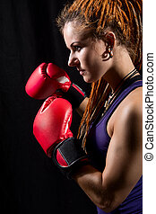 Beautiful woman with red boxing gloves, dreadlocks on a black ba