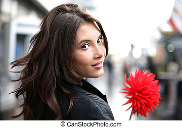 Beautiful woman with red flower looking back - Beautiful...