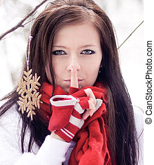 Beautiful woman with red gloves in winter forest.