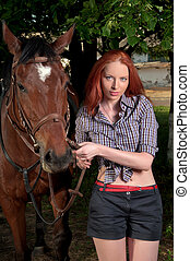 woman with red hair standing next to horse