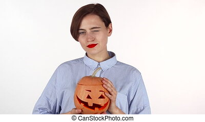 Beautiful woman with red lips smiling happily, holding Halloween pumpkin