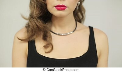 Beautiful woman with red lipstick puts a finger to her lips
