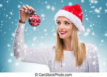 Beautiful woman with santa hat holding red Christmas Ornament
