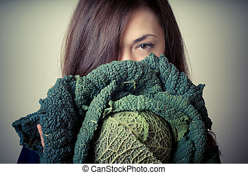 beautiful woman with savoy cabbage on gray background