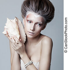 Beautiful woman with seashell posing isolated. Series of photos