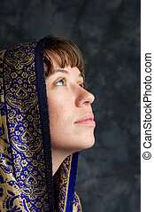 Portrait of a beautiful brown haired woman in profile, looking up as if in prayer, her head is wrapped in an exotic shawl.