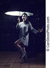 Beautiful woman with silver dress dancing in rain under an umbrella at night
