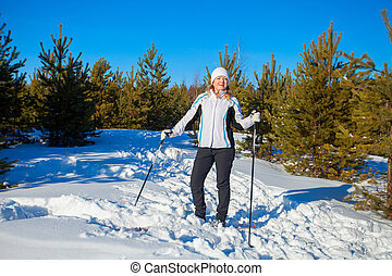 beautiful woman with skis in  winter forest