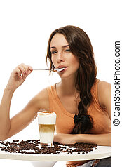 beautiful woman with spoon in her mouth sitting at a table with latte macchiato coffee on white background