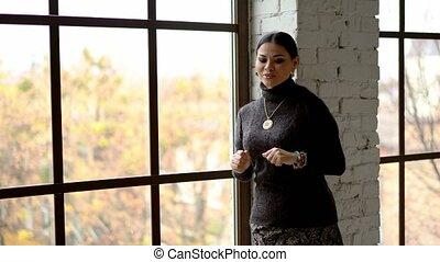 Beautiful woman with straight black hair is dancing near the window.