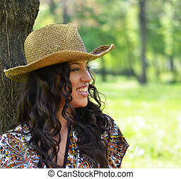 Beautiful woman with straw hat leaned against tree