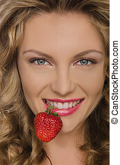 Beautiful woman with strawberry teeth