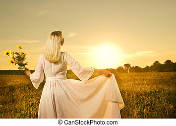 Beautiful woman with sunflowers in the field at sunset