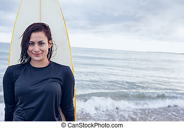 Beautiful woman with surfboard at beach