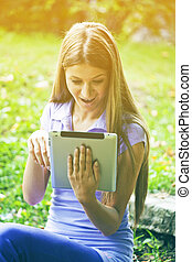 Beautiful Woman With Tablet Computer In Park