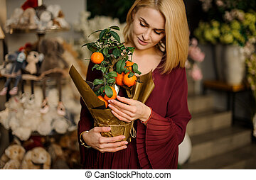 Beautiful woman with tangerine tree in pot