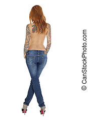 Beautiful woman with tattoos on back and blue jeans