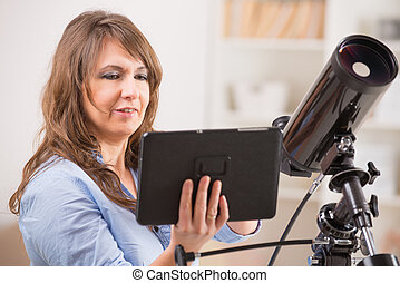 Beautiful woman with telescope and tablet