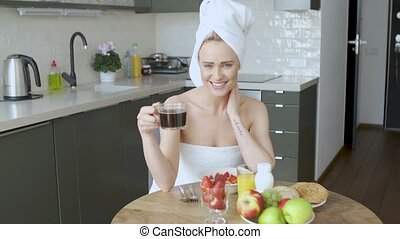 Beautiful woman with towel on head having a healthy breakfast and coffee