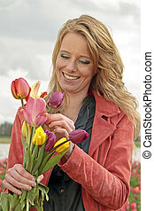 beautiful woman with tulips in the fields