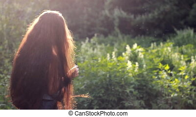 Beautiful woman with very long hair in the sunglasses at sunset.