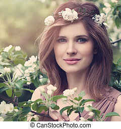Beautiful Woman with White Apple Flowers. Cute Face, Natural Makeup. Young Beauty