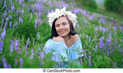 Beautiful woman with white flower wreath in violet field....