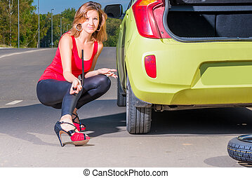 beautiful woman with with a wrench near the the green car