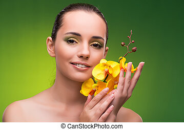 Beautiful woman with yellow orchid flower