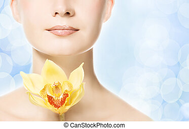 Beautiful woman with yellow orchid over abstract blue background